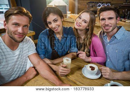 Portrait of happy friends having coffee in café