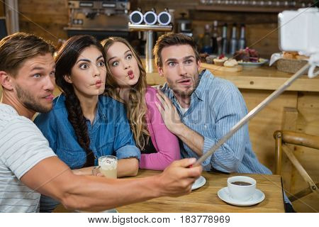 Happy friends taking selfie on mobile phone while having coffee in café