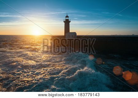 Ocean surf on the Atlantic coast, near lighthouse during a beautiful sunset, Porto, Portugal.