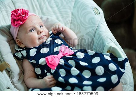 Infant lies in the armchair for toddlers. Baby is dressed in a beautiful dress.