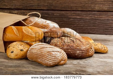 Various bread loaves in bag on wooden background
