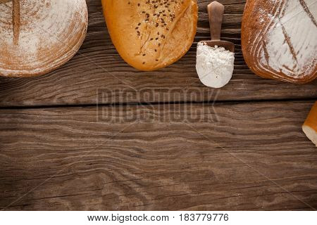 Various bread loaves with scoop of flour on wooden background