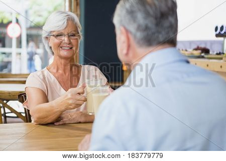 Senior couple toasting glasses of cold coffee in cafe
