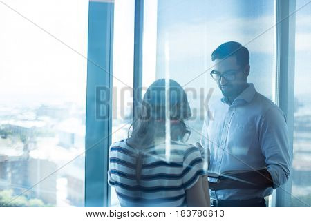 Business couple reading book in office seen through glass