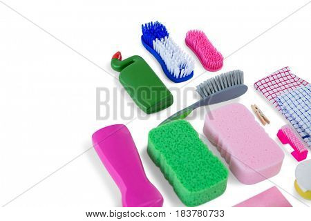 High angle view of various sponges and brushes with cleaning products on  white background