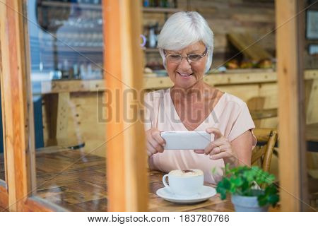 Senior woman photographing a coffee cup in cafe