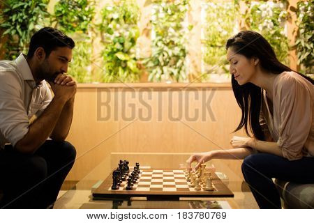 Business colleagues playing chess in office