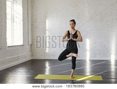 Tree Pose for to find the Balance. Sports asian young woman standing in the yoga pose Vrksasana with closed eyes in training yoga hall. Businesswoman engaged in yoga in the morning before workday