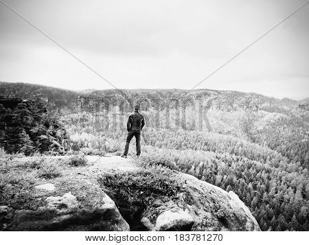 Hiker In Sportswear Stand On  Rock And Watching Over Autumnal Colorful Valley To Sun