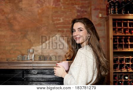 Pretty young woman with cute smile sitting against old brick wall in the bar with coffee cup looking at the camera and smiles to compliments in her address. Copy space for promotional content