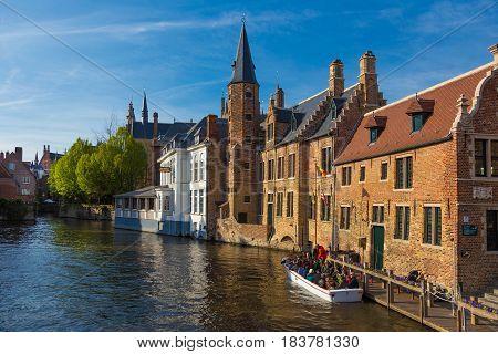 Bruges Belgium - 11 April 2017 - Tourists get on small tour boat on river of Bruges Belgium on April 11 2017