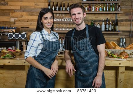 Portrait of smiling waiter and waitresses standing at counter in cafe