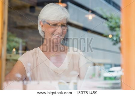 Happy senior woman using mobile phone in cafe