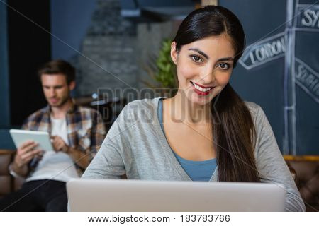 Portrait of young woman using laptop in cafe