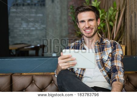 Portrait of young man using digital tablet while relaxing on sofa in café