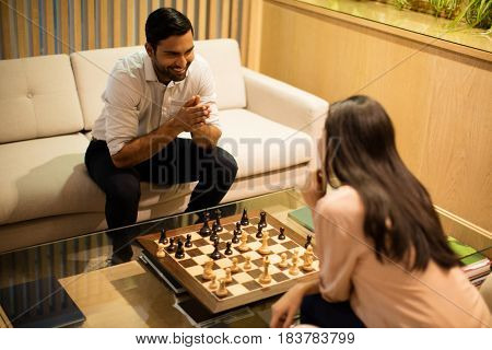 High angle view of smiling business colleagues playing chess in office