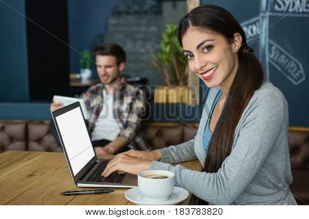 Portrait of young woman using laptop while having coffee in cafe