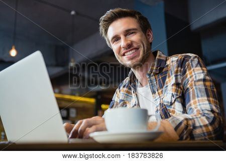 Portrait of happy young man using laptop while having coffee in cafe