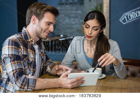 Young couple using digital tablet while having coffee in cafe