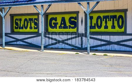 Slots, Gas, Lotto Sign On Side Of Abandoned Building