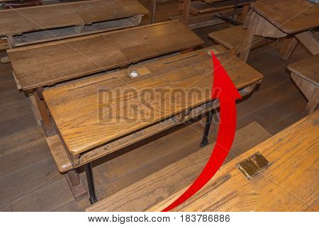 Old classroom with school desks and a red arrow. Concept failure examination to the high school failed.