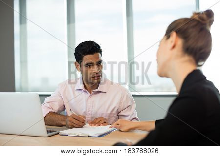 Business people discussing contract during meeting in conference room
