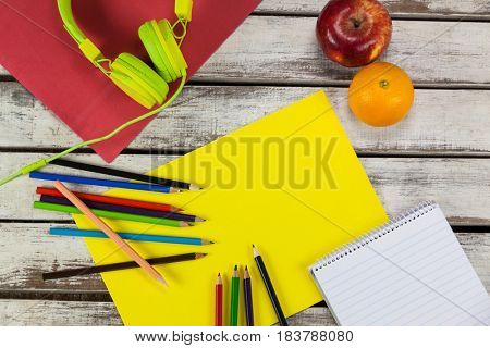 Color pencils, notepad, placard, fruits and headphones on wooden plank