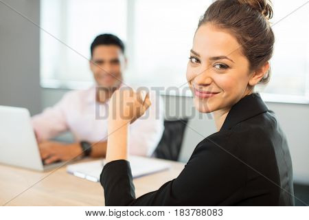 Portrait of smiling businesswoman sitting at table with colleague in background