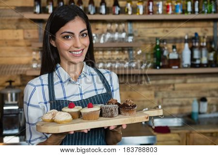 Portrait of smiling waitress holding cupcakes in wooden tray at counter in cafe