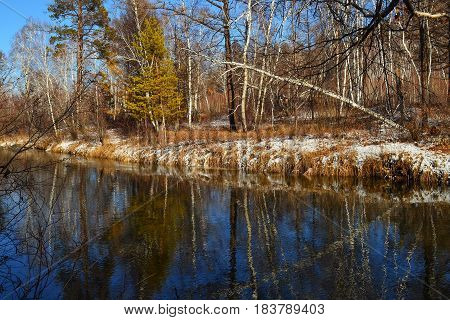 scenery around autumn river. On the mirror-smooth water the reflections of the trees visible