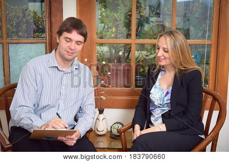 Business people - young attractive woman and successful man - discussing document in the office
