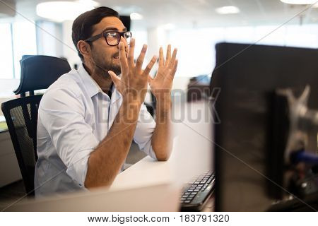 Frustrated businessman clenching teeth while sitting in office