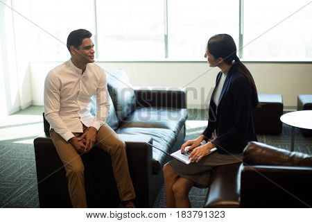 Businessman ineracting with female colleague while sitting on sofa at office