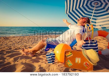 Happy Young Man Sitting On The Beach