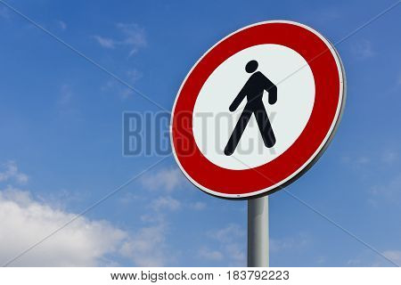 Walking forbidden sign on a blue sky with clouds