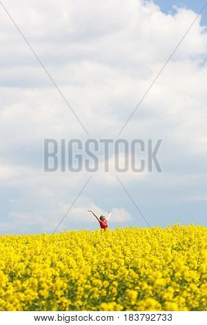 Woman with arms raised high enjoying freedom in vibrant rapeseed field with big blue sky in the background. Happiness emancipation natural living and freedom concept with copy space.