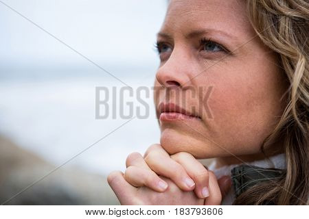 Close-up of thoughtful woman with hands clasped at the beach
