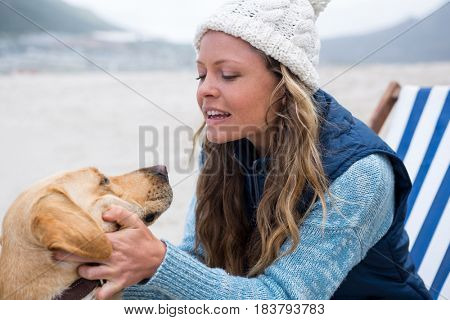 Woman pampering dog while sitting on chair at the beach