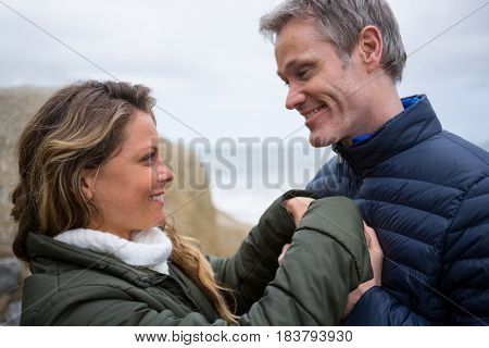 Happy romantic couple embracing face to face on the beach