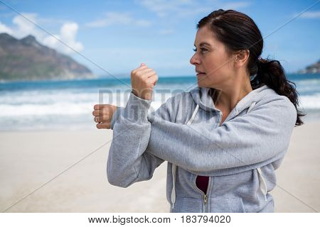 Mature woman performing stretching exercise on beach