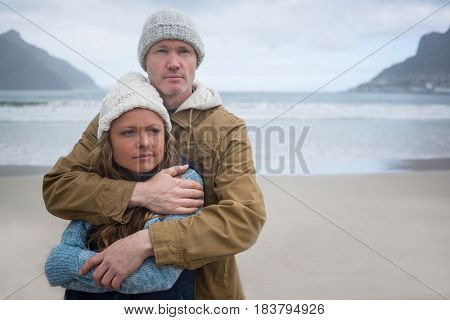 Couple hugging each other while standing at the beach