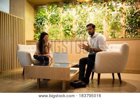 Business colleagues discussing while sitting on sofa in illuminated office