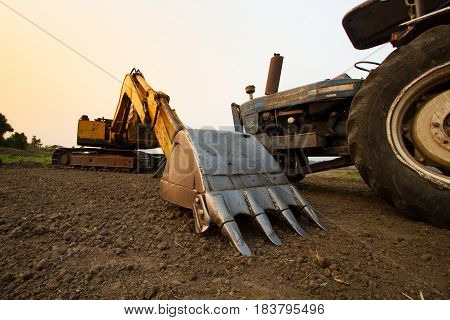 Backhoe and Tractor prepare land for cultivation with sunset sky