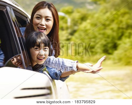 happy asian mother and daughter having fun while riding in family car.