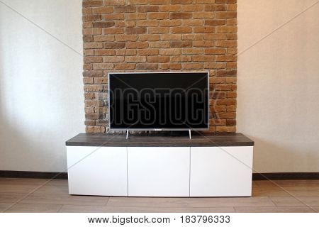 Bedside table under the TV against a brick wall