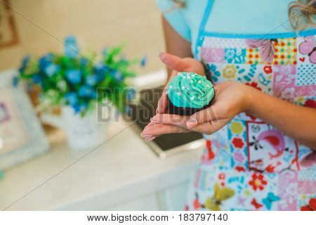 Muffin blue color in the women's hands. Cooking cupcakes in the kitchen