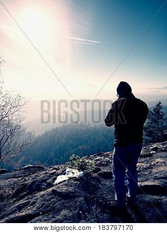 Tall  Man Is Taking Photo By Mirror Camera On Neck. Snowy Rocky Peak Of Mountain.