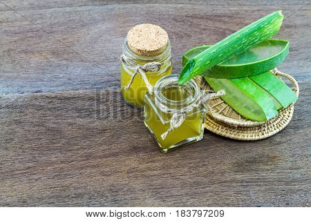 Fresh aloe vera gel with aloe vera essential oil on wooden table