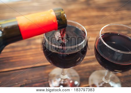 pouring red wine from bottle into two glasses