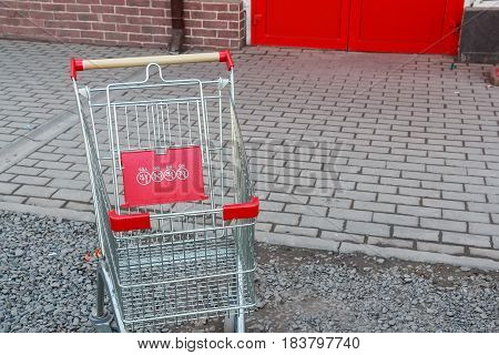 Close-up of a red trolley outside grocery store on pavement